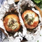 Two roasted onions in a baking tin surrounded by foil