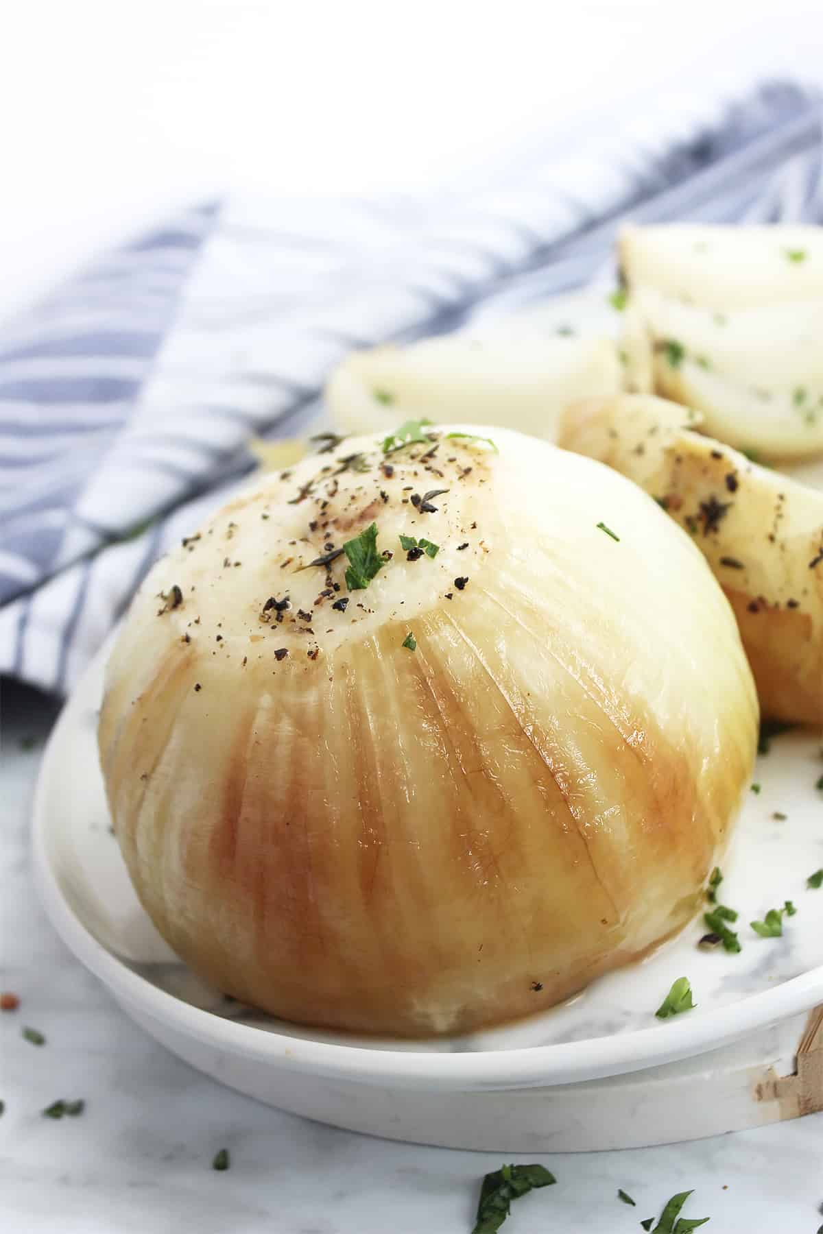 A whole roasted onion on a serving plate