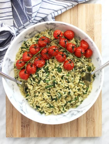 A bowl of orzo pasta salad on a chopping board
