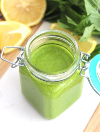 A jar of lemon basil pesto next to fresh lemon and basil leaves