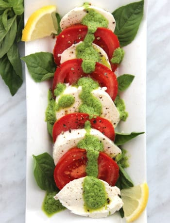 Overhead shot of pesto caprese salad on a white serving plate.