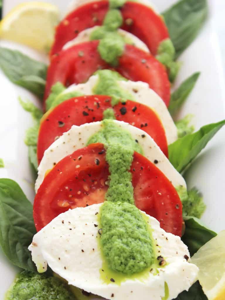 Pesto caprese salad garnished with lemon slices and basil leaves.