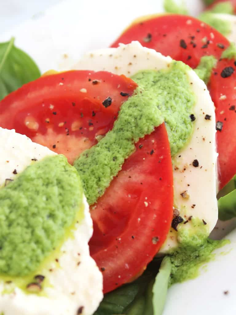 Close up of mozzarella and tomato slices with pesto.
