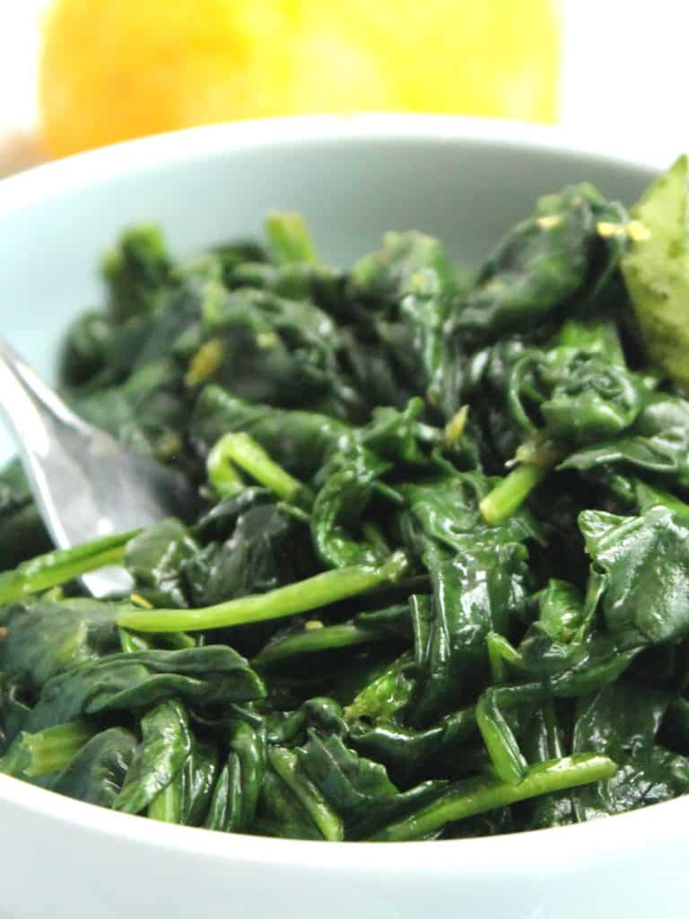 Close up of a fork in a bowl of wilted spinach.