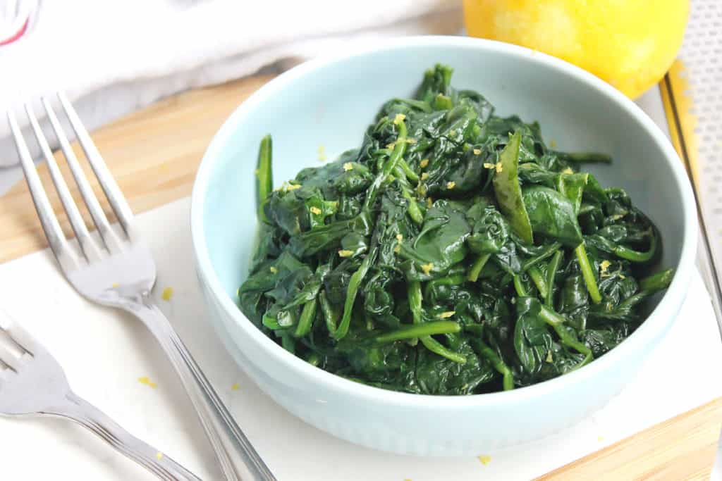 A bowl of buttered garlic spinach next to two forks.