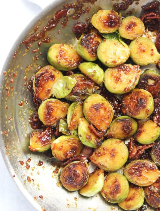 Close up of halved Brussel sprouts in a skillet in sauce.