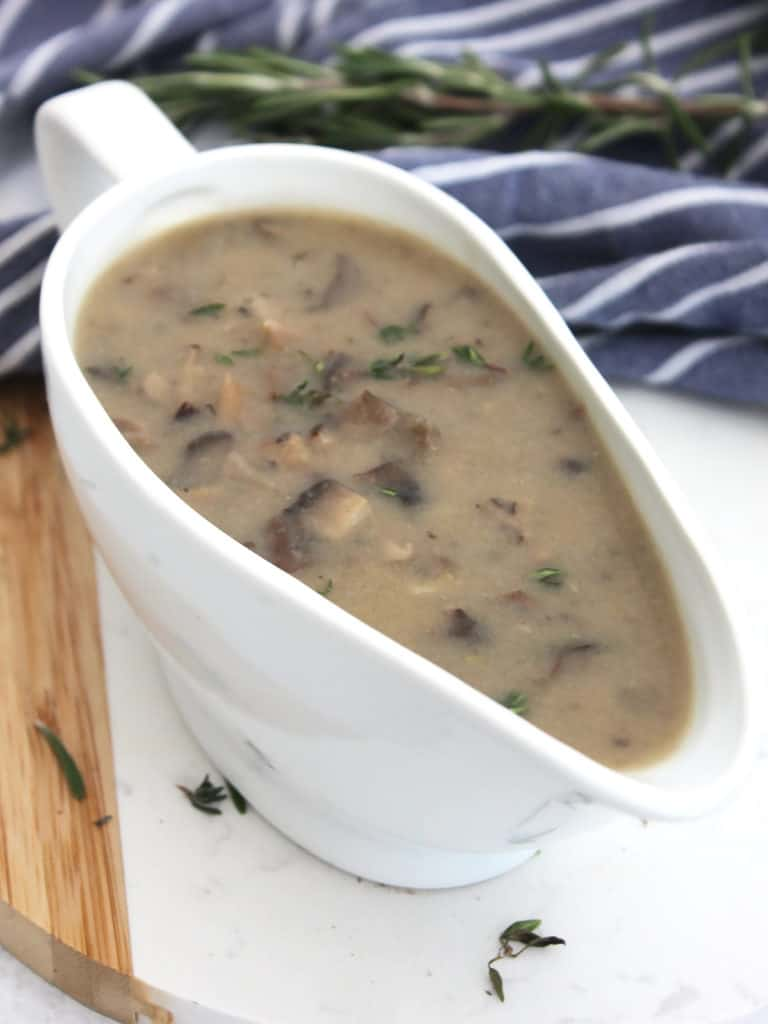 A boat of gravy in front of fresh rosemary and a blue and white cloth.