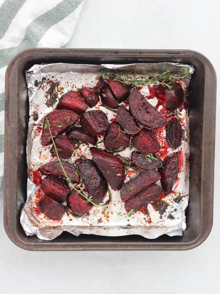 The roasted beet wedges in a baking sheet next to a white and green cloth.