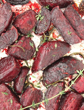 Roasted beet wedges on foil with fresh sprigs of thyme.