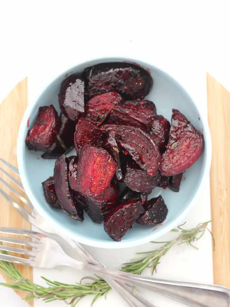 Beet wedges served in a bowl next to a sprig of rosemary and two forks.