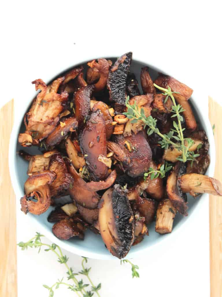 Fresh thyme garnish in a bowl of roasted mushrooms.
