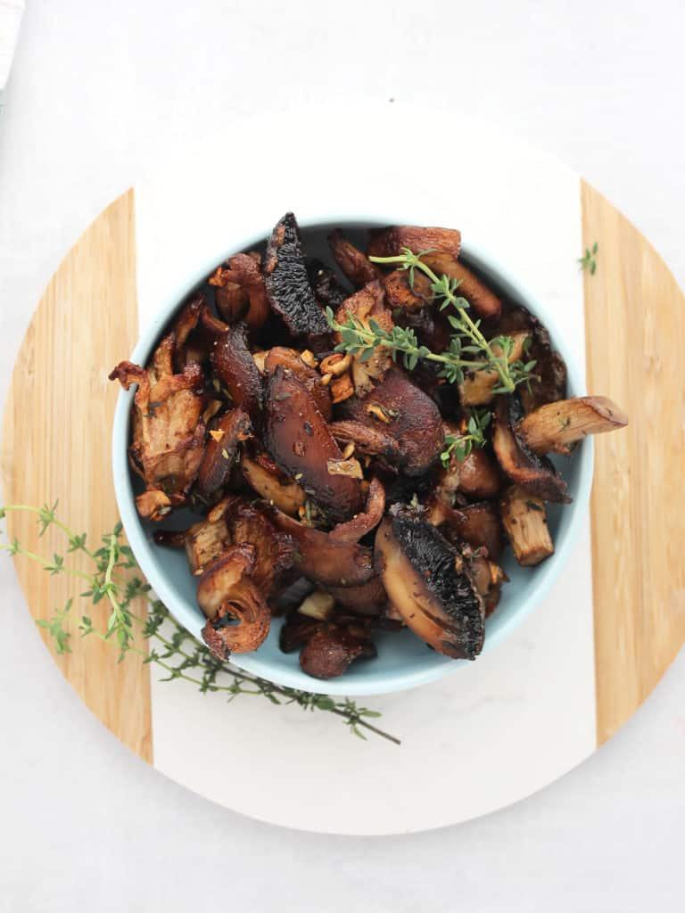 A bowl of roasted mushrooms on a white and wood chopping board.