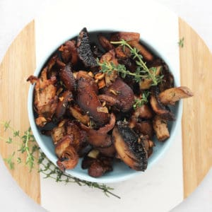 Garlic roasted mushrooms in a blue bowl garnished with fresh thyme.