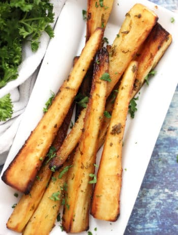 Honey mustard glazed parsnips on a white plate next to a bunch of parsley.