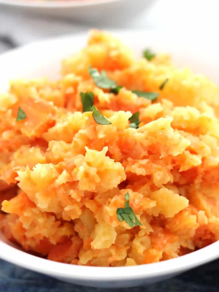 Close up of rutabaga carrot mash and fresh parsley garnish.