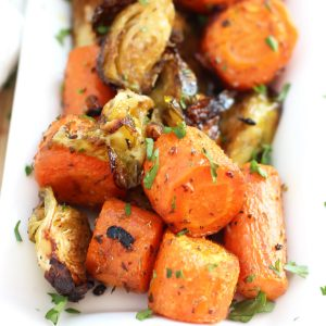 Close up over roasted carrots and Brussels garnished with fresh herbs.