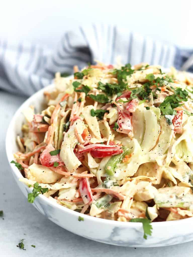 Slaw with sliced bell peppers, carrots and cabbage topped with fresh herbs.