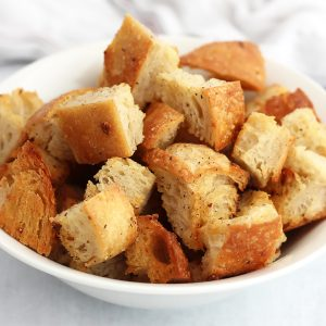 Garlic butter croutons in a white bowl.