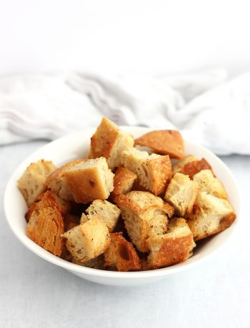 A bowl of garlic butter croutons in front of a white cloth.