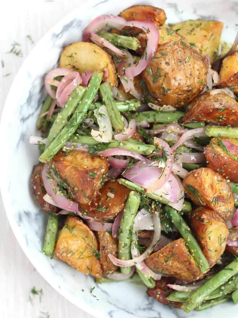 Roasted potato salad with vegetables in a bowl.