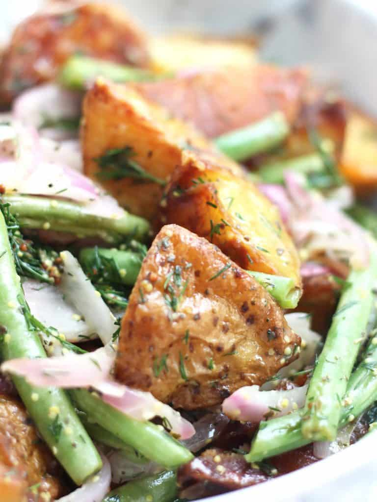 Close up of roasted potatoes on top of green beens and dressed with a vinaigrette.
