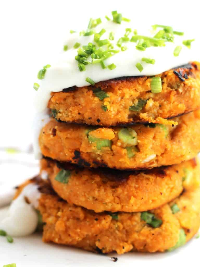 Four sweet potato cakes stacked on top of each other with sour cream and chopped chives.