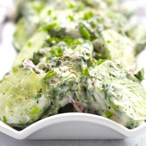 Close up of creamy cilantro cucumber salad on a long serving plate.