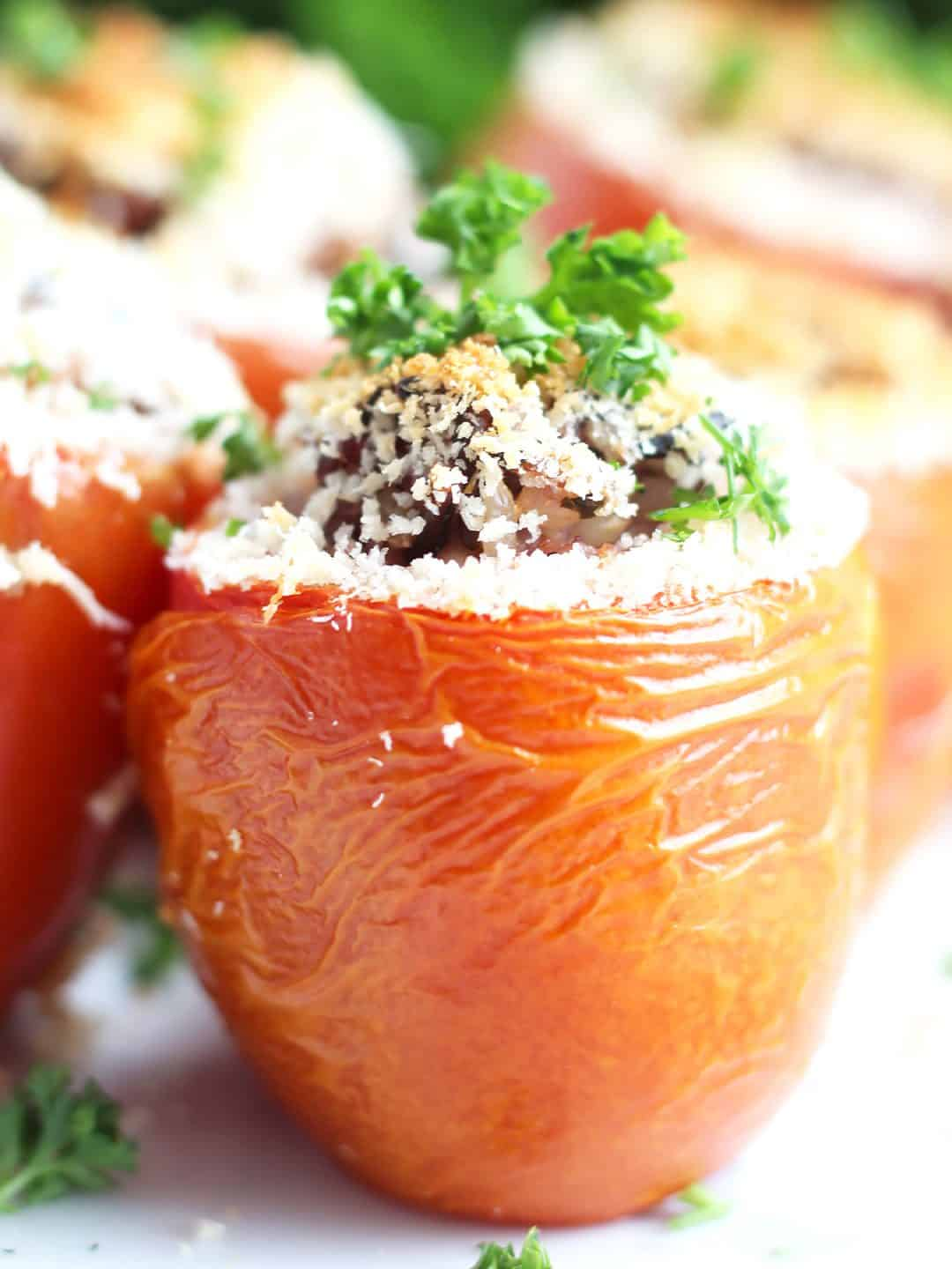 Close up of a wild rice stuffed tomato garnished with chopped parsley.