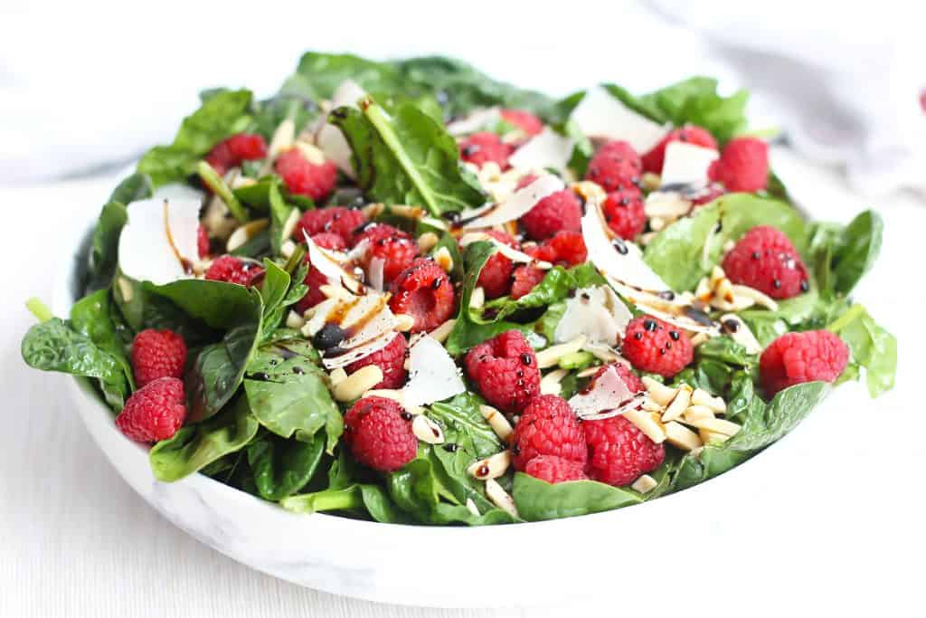 Side view of a spinach raspberry salad in a large white bowl.