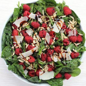Overhead shot of the spinach raspberry salad with balsamic glaze.