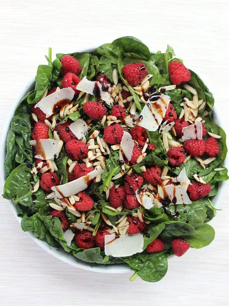 Overhead shot of the spinach raspberry salad in a serving bowl.