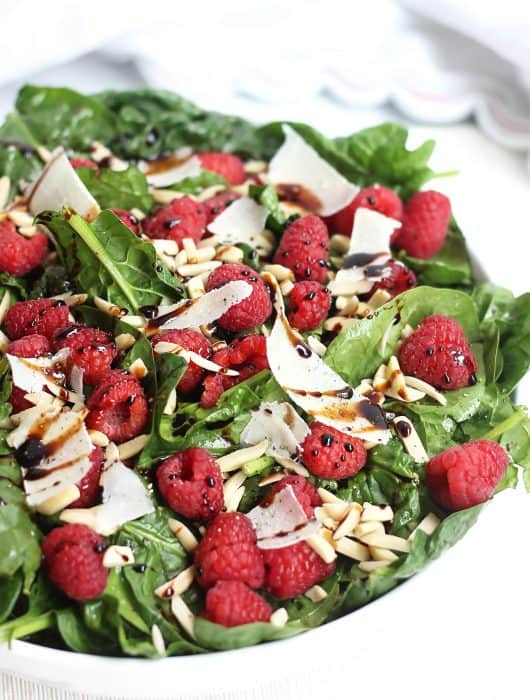 Shaved parmesan and raspberries on a bed of baby spinach and drizzled with balsamic.