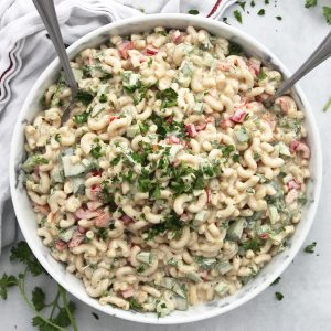 Cajun pasta salad in a serving bowl with two spoons.