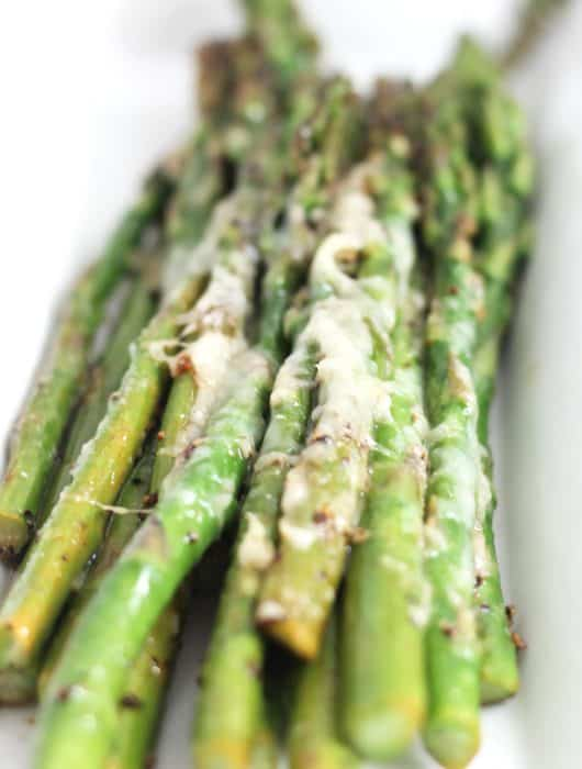 Close up of the melted cheese on the cooked asparagus spears.