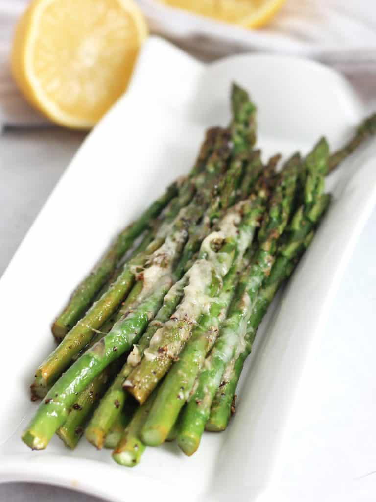 Sauteed asparagus with parmesan and lemon on a white serving plate.