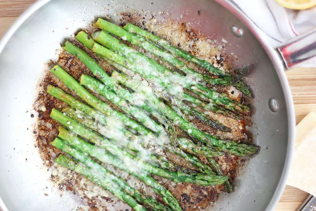 The cooked asparagus in a skillet topped with parmesan cheese.