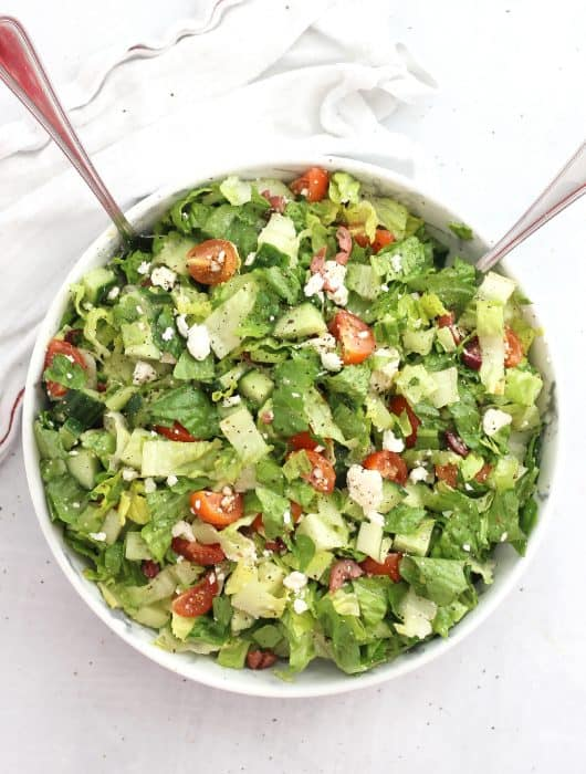 Overhead shot of lettuce Greek salad served in a large bowl.