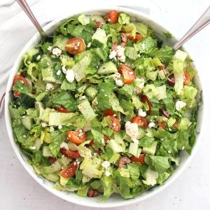 Lettuce Greek salad served in a large bowl with two spoons.