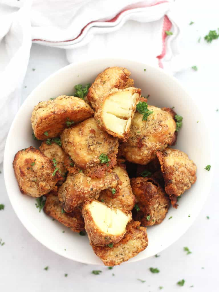 Overhead shot of the parmesan crusted roasted potatoes in a bowl garnished with fresh herbs.