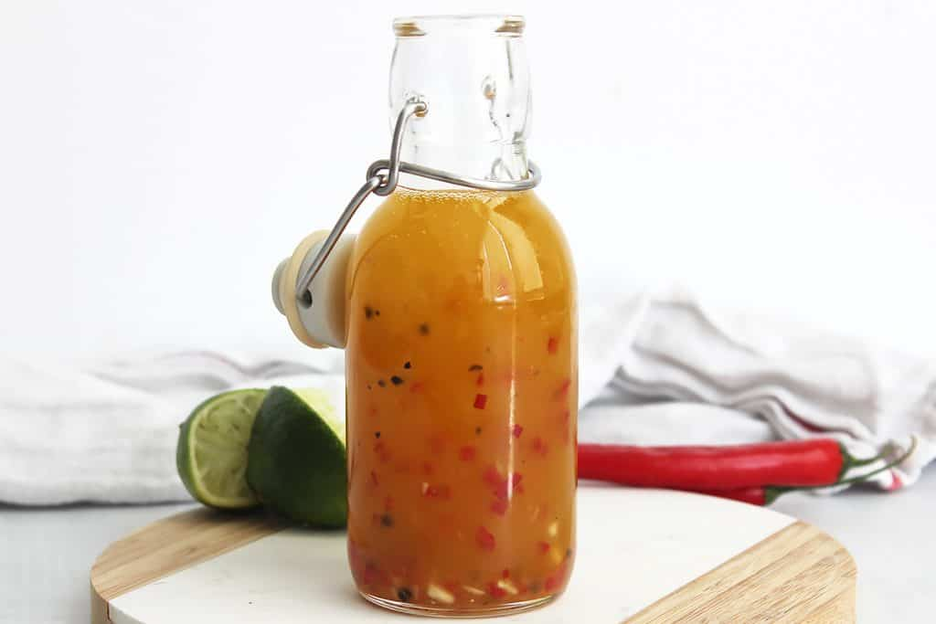 Chili lime dressing in a bottle next to fresh limes and red chilies.