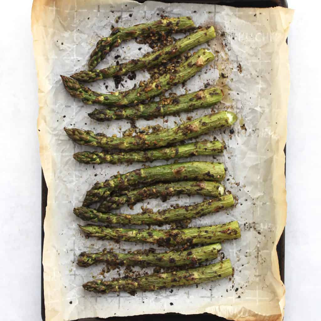Roasted pesto asparagus on a parchment lined baking sheet.