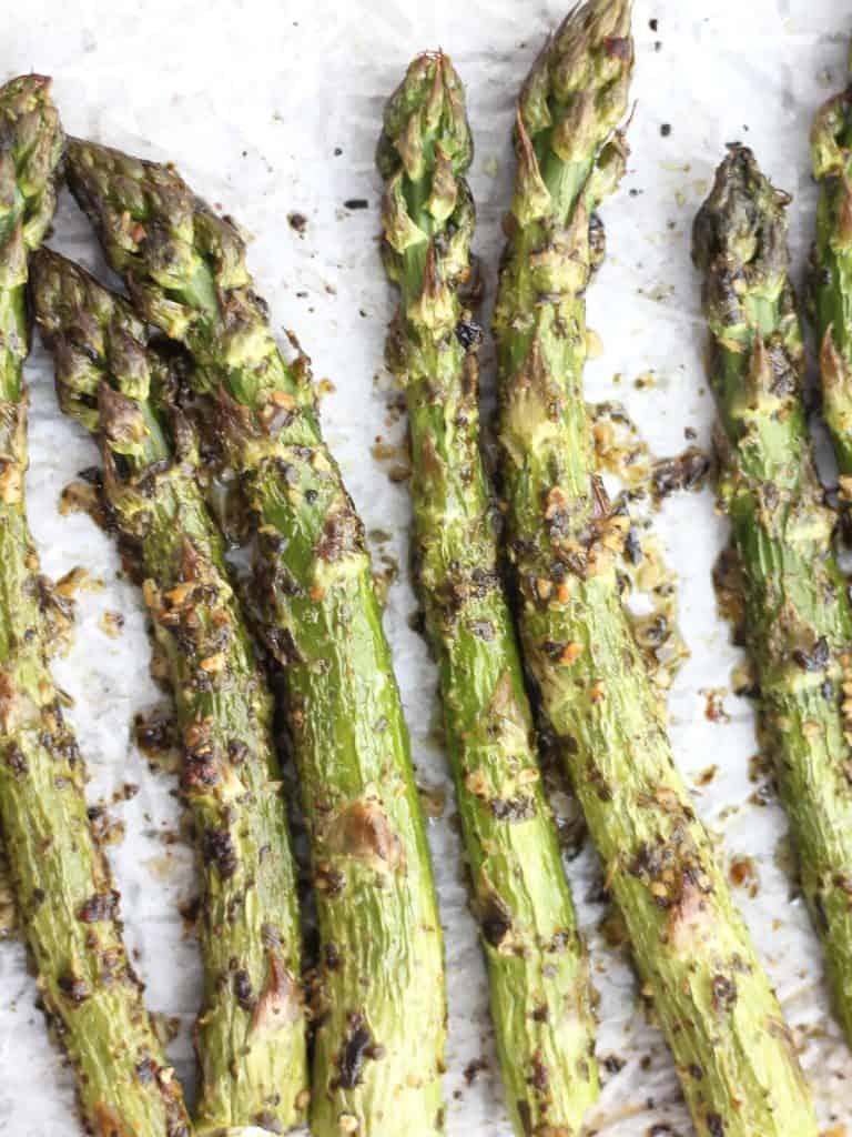 Six roasted asparagus spears on parchment.
