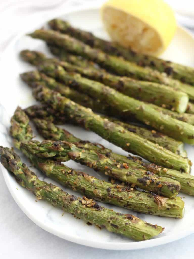 Roasted pesto asparagus served on a plate with a fresh lemon wedge.