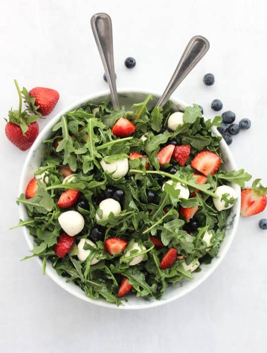 Red white and blue salad in a large serving bowl with two spoons.