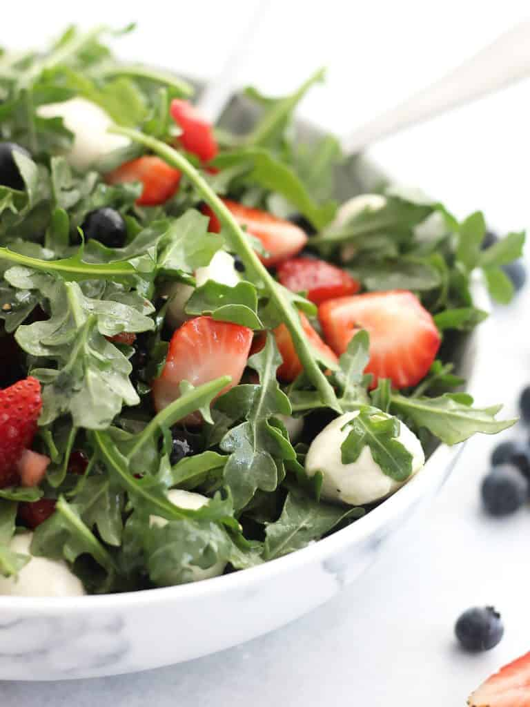Close up of the arugula tossed with berries and mozzarella.