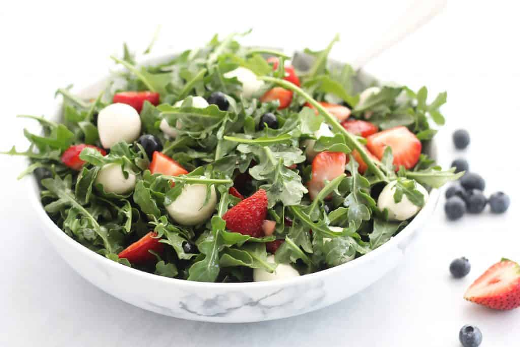 Red, white and blue salad in a serving bowl next to fresh berries.