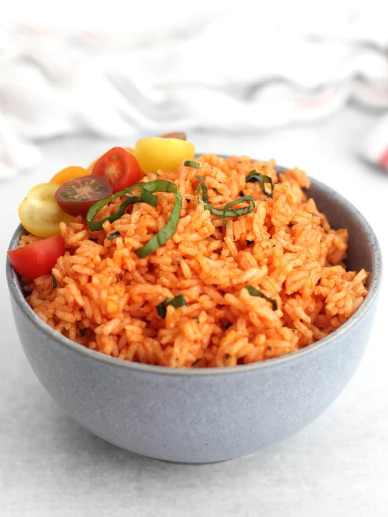 Freshly cooked tomato and basil rice served in a blue bowl.