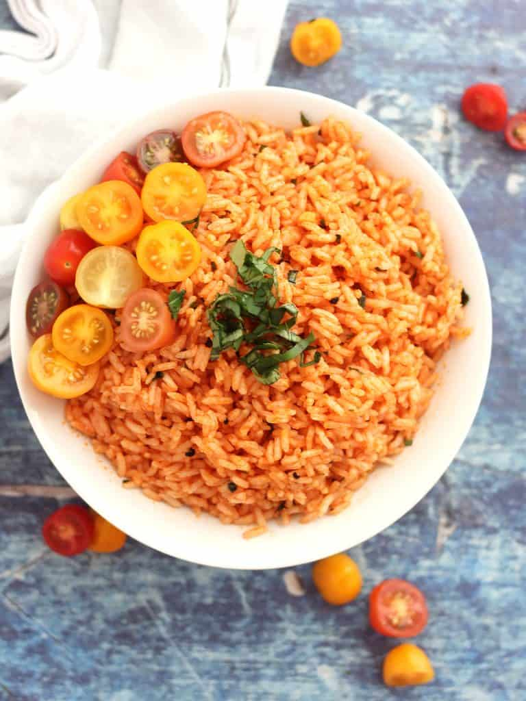 Red rice topped with fresh tomatoes and fresh basil in a white bowl.