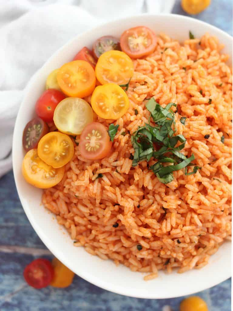 Red rice topped with halved tomatoes and fresh basil.
