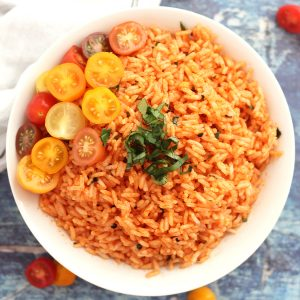 Tomato rice in a white bowl, garnished with halved cherry tomatoes and fresh basil.
